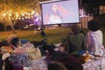 Amigos assistindo filme na tela de projeção no quintal — Fotografia de Stock