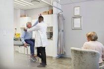 Врач, осматривающий старшего пациента мужского пола в экзаменационной комнате — стоковое фото