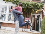Feliz, pareja emocionada abrazando y celebrando fuera de casa nueva - foto de stock