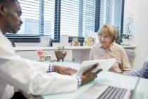 Врач с цифровым планшетом разговаривает со старшим пациентом в кабинете врача — стоковое фото