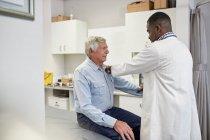 Paciente sênior de exame do doutor masculino no quarto da examinação da clínica — Fotografia de Stock