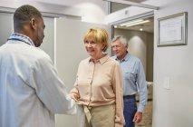 Medico saluto coppia senior in clinica medici ufficio — Foto stock