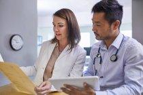 Médecins discutant du dossier médical à la clinique — Photo de stock