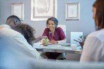 Женщина-врач дает конфеты девушке в офисе врача — стоковое фото