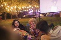 Amigos saindo, assistindo filme no quintal — Fotografia de Stock