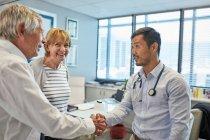 Doutor masculino que agita as mãos com pares sênior no escritório dos doutores da clínica — Fotografia de Stock