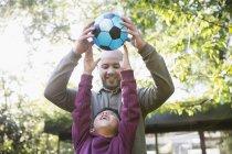 Pai e filho jogando futebol no parque ensolarado — Fotografia de Stock