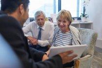 Врач с цифровым планшетом разговаривает со старшей парой в кабинете врача клиники — стоковое фото