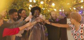Друзі відзначати, тотажних шампанське на вечерю сад партії — стокове фото