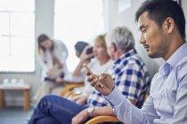 Man using smart phone, waiting in clinic waiting room — Stock Photo
