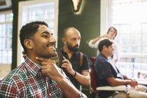 Sorridente cliente maschio controllo viso rasato in barbiere — Foto stock