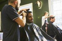 Улыбающийся мужчина стрижется в парикмахерской — стоковое фото
