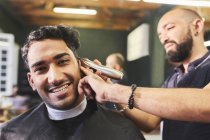 Ritratto giovane e sorridente che riceve un taglio di capelli dal barbiere — Foto stock