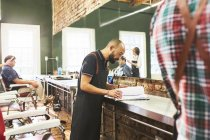 Male barber looking at schedule in barbershop — Stock Photo