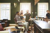 Barbieri e clienti maschili in barbiere — Foto stock