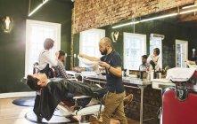 Мужской парикмахер готовится к пару лицо клиента перед бритьем в парикмахерской — стоковое фото