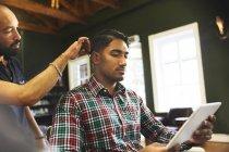 Uomo che utilizza tablet digitale mentre riceve taglio di capelli in barbiere — Foto stock