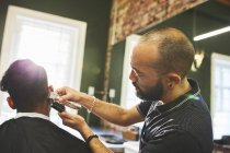 Barbeiro masculino com aparadores dando corte de cabelo ao cliente na barbearia — Fotografia de Stock