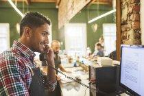 Hombre peluquero hablando por teléfono en el ordenador en la barbería — Stock Photo