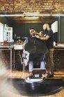 Мужчина парикмахер бритья лицо клиента в парикмахерской — стоковое фото