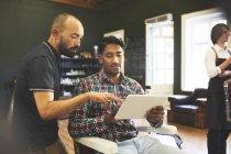 Мужчина парикмахер и клиент с цифровой планшет говорить в парикмахерской — стоковое фото