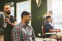 Мужчина парикмахер держит зеркало для улыбающегося клиента в парикмахерской — стоковое фото