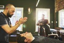 Парикмахер, стоящий над клиентом в парикмахерской — стоковое фото