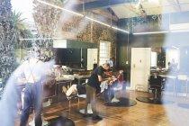 Male barber shaving face of customer in barbershop — Stock Photo