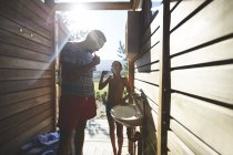 Father and son brushing teeth in sunny campsite bathroom — Stock Photo