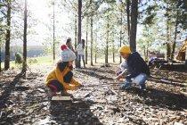 Fratello e sorella che si radunano accendendosi nei boschi soleggiati fuori dal campeggio — Foto stock