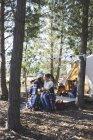 Счастливая, любящая лесбийская пара с детьми, расслабляющая, пьющая кофе в кемпинге в лесу — стоковое фото