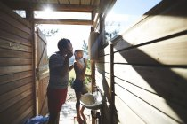 Father and son brushing teeth at sunny campsite bathroom mirror — Stock Photo