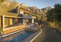 Mountains behind sunny luxury home showcase exterior house with swimming pool — Stock Photo