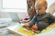 Cute curieuse petite fille lisant un livre d'images — Photo de stock