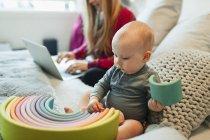 Curieuse petite fille jouant avec un jouet sur le lit pendant que sa mère travaille sur un ordinateur portable — Photo de stock