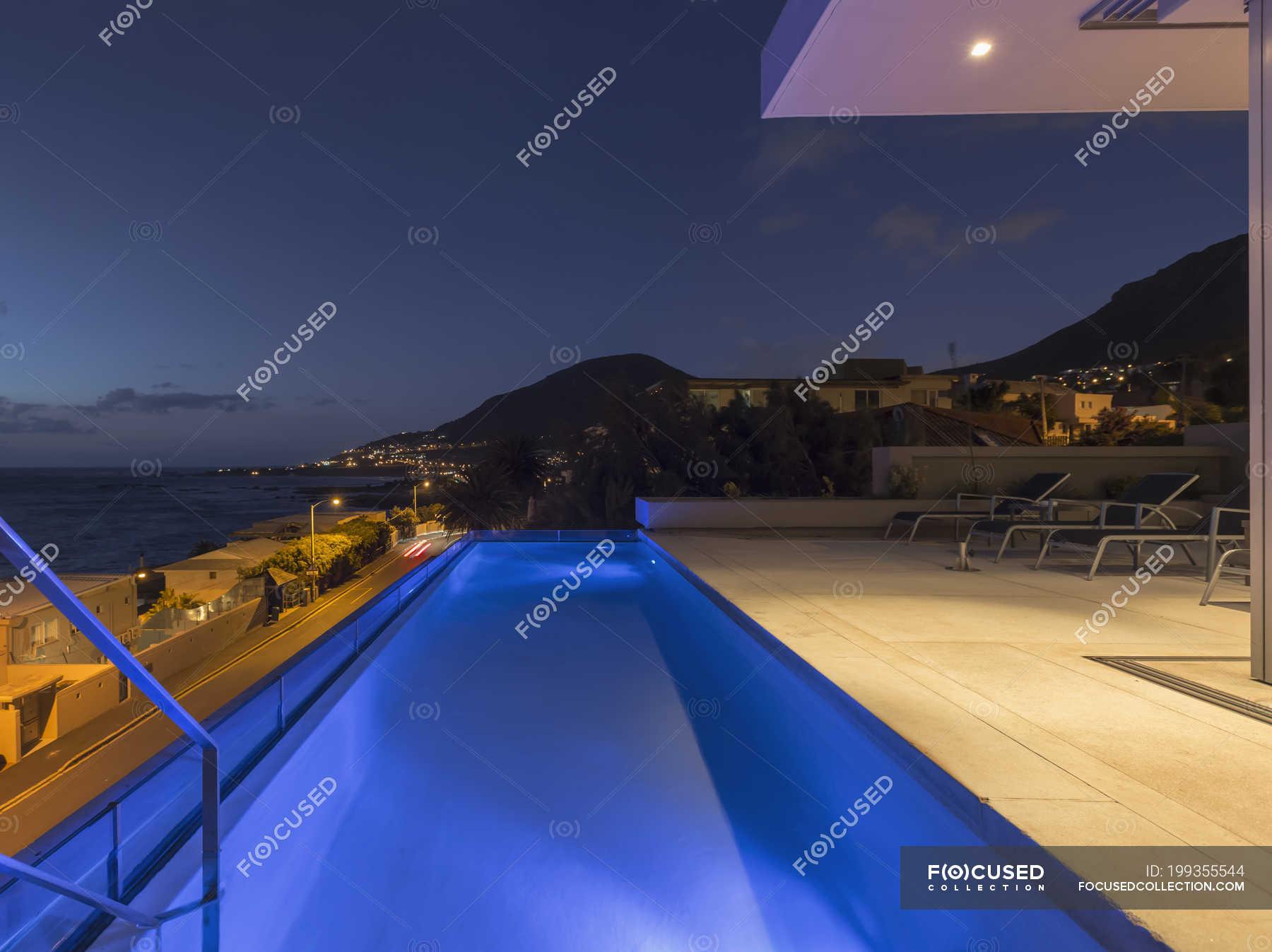 Illuminated blue lap swimming pool on luxury patio at night ...