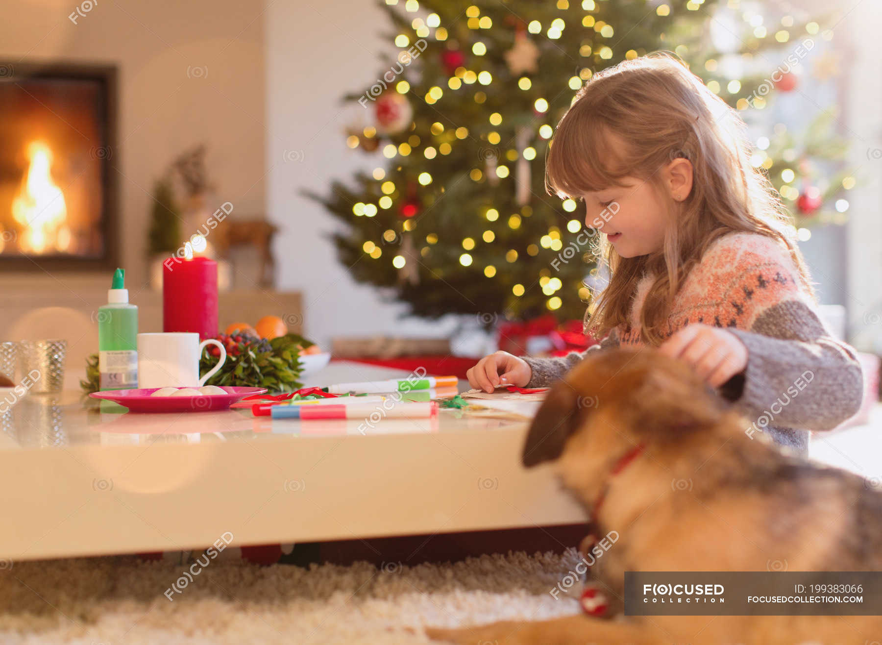 Dog watching girl coloring with markers in Christmas living ...