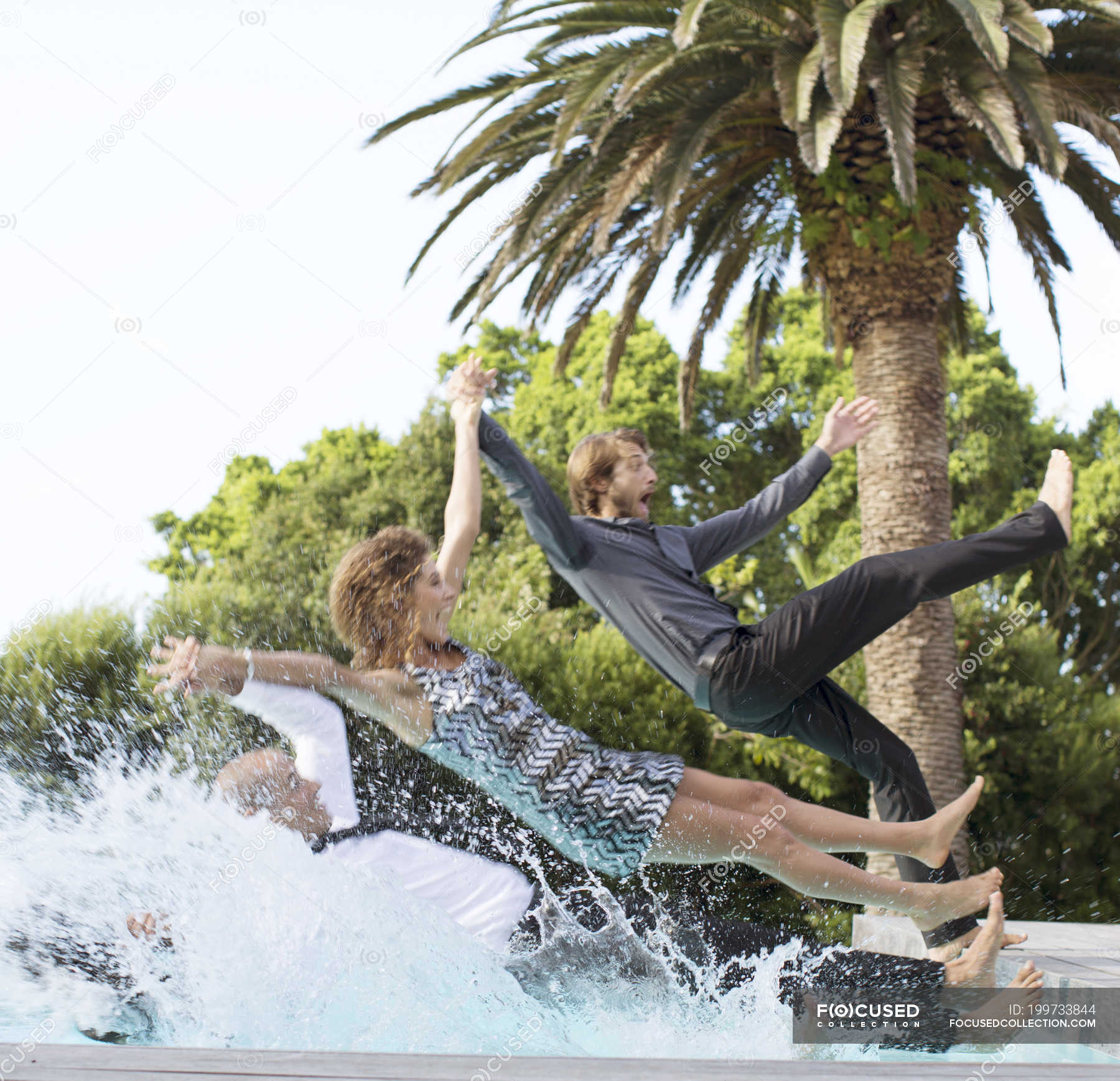 Friends jumping backwards into swimming pool — side view