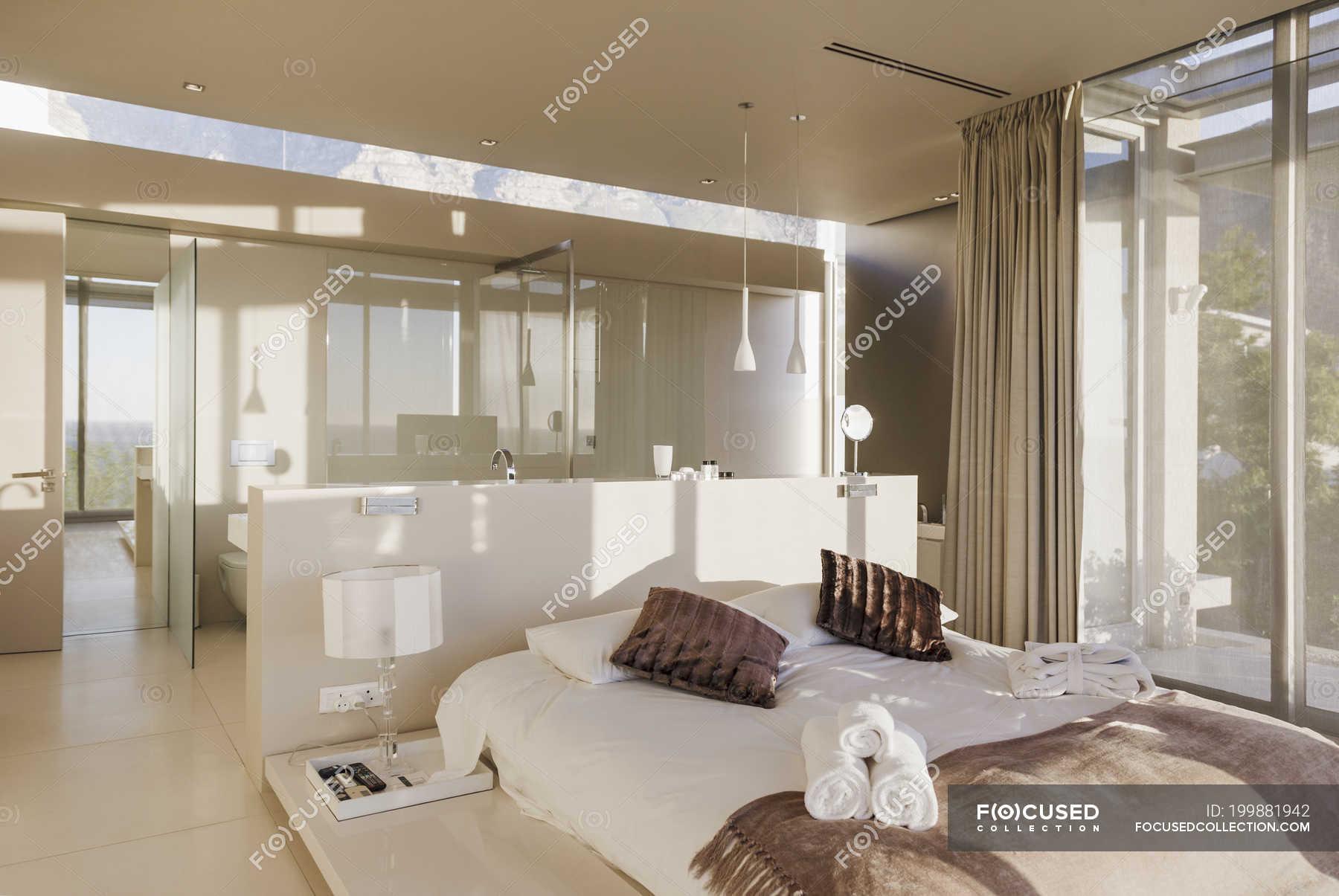 Bed and bathroom in modern master bedroom — real estate, travel