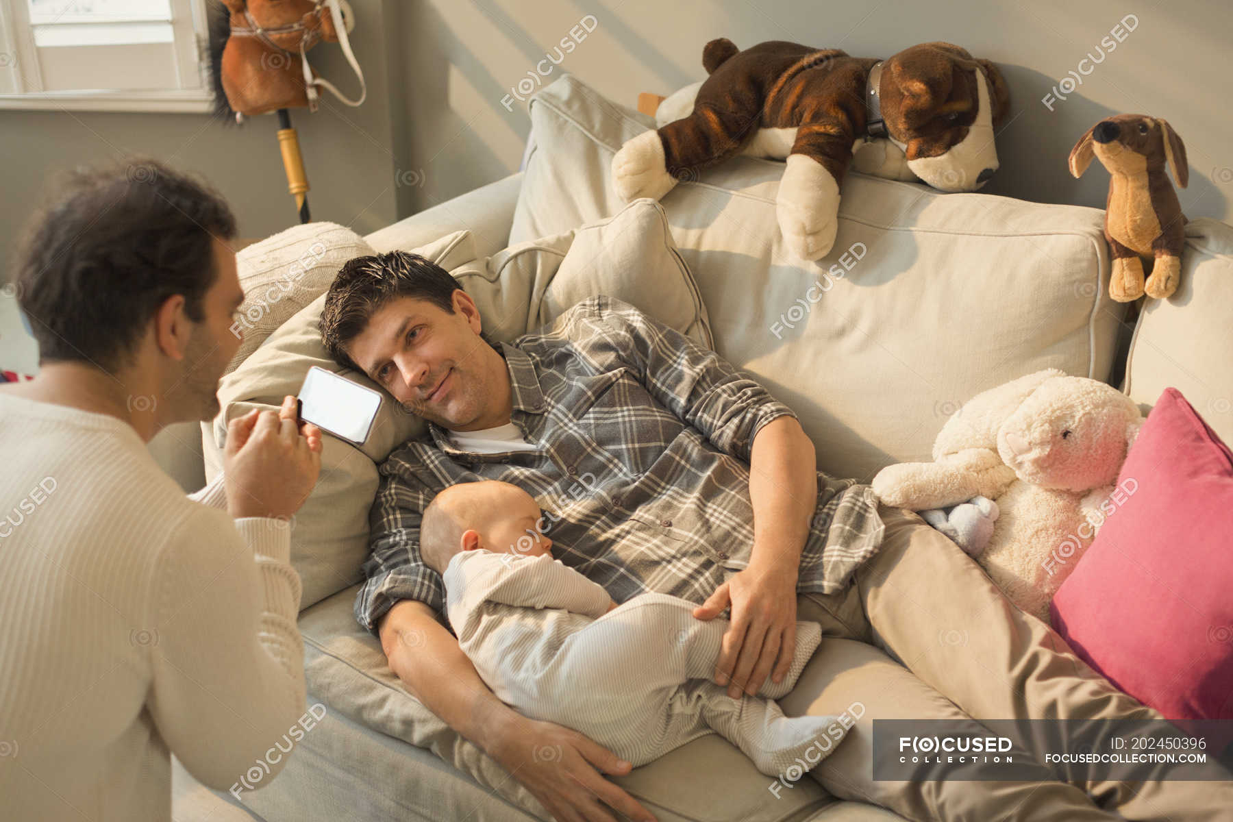 Male Gay Parents And Baby Son Resting On Living Room Sofa High