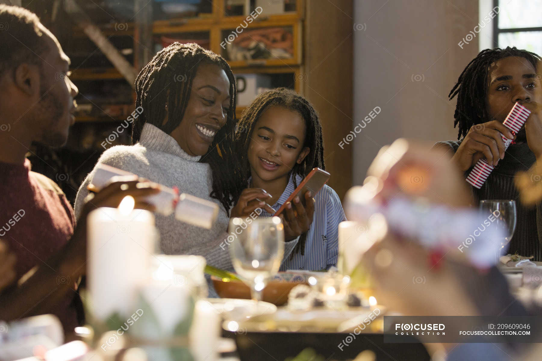 Mother and daughter using smart phone at Christmas dinner