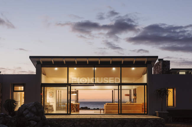 Iluminada casa de luxo sob o céu ao entardecer — Fotografia de Stock