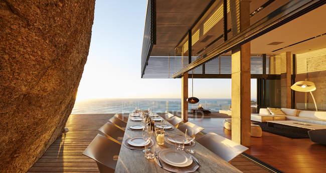 Moderne Luxus Terrasse Esstisch mit Blick auf den Sonnenuntergang Ozean — Stockfoto