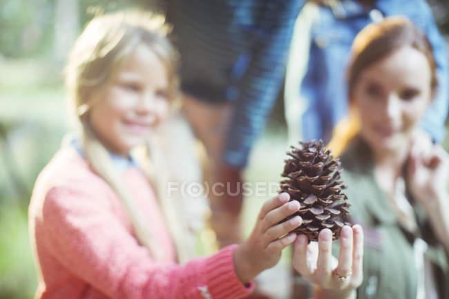 Étudiants et enseignants tenant un cône de pin en forêt — Photo de stock
