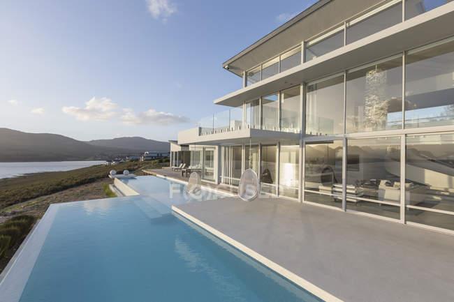 Sunny, tranquilo casa de luxo moderno vitrine exterior com piscina infinita — Fotografia de Stock