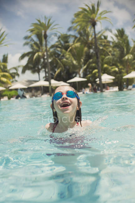 Portrait playful girl swimming with swim goggles in sunny tropical ocean — Stock Photo