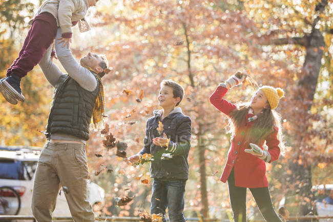 Playful father and children playing in autumn leaves — Stock Photo