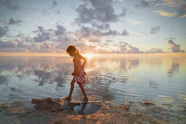Mädchen watet in der Brandung des Ozeans am ruhigen Sonnenuntergang Strand — Stockfoto