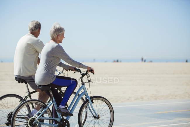 Coppia senior in bicicletta sulla spiaggia — Foto stock