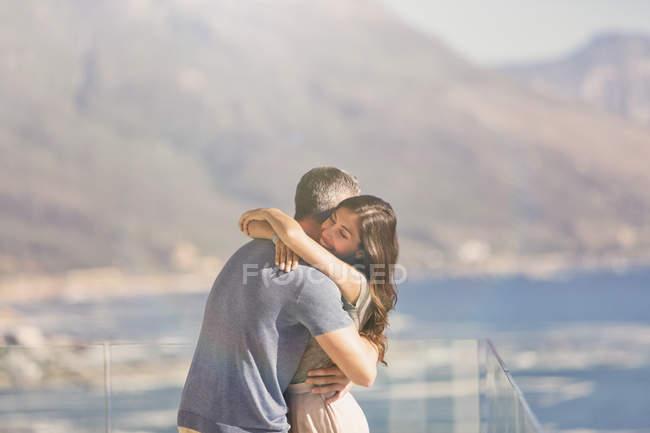 Casal afetuoso abraçando na varanda com vista para o mar e montanha — Fotografia de Stock